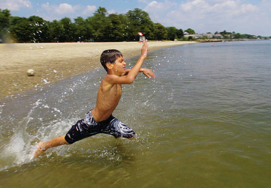 Hour photo / Erik Trautmann Christian Iosifides, 7, splashes into the waters at Calf Pasture Beach to escape the high heat and humidity Tuesday. / (C)2011, The Hour Newspapers, all rights reserved