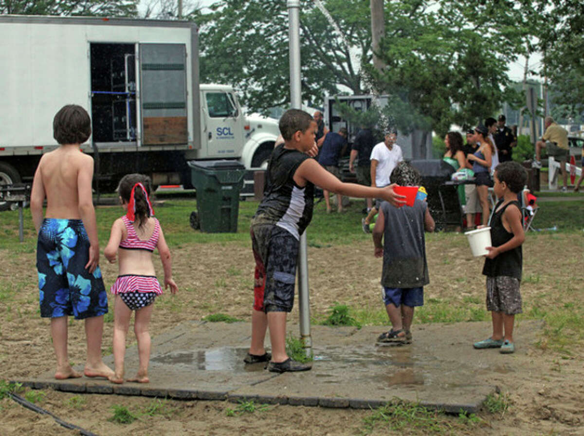Children enjoy the running water at Shady Beach in Norwalk Sunday afternoon.