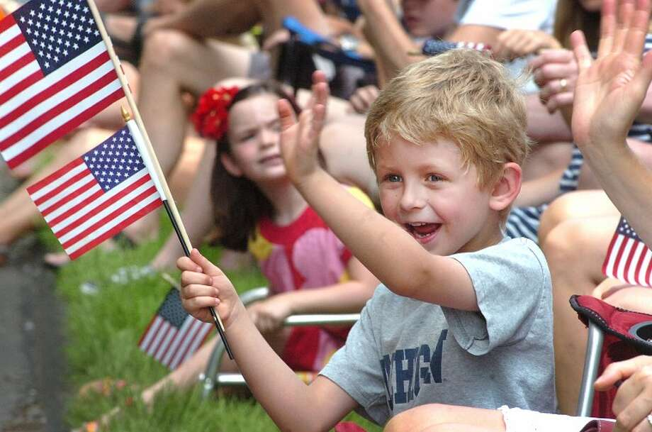 Hour Photo/ Alex von Kleydorff. 6yr old Ryan Cohen waves to a friend in a girl scout troop during Wiltons memorial day parade.
