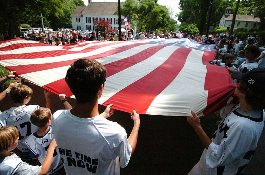 Hour Photo/ Alex von Kleydorff. Wiltons Lacrosse teams carry a giant American Flag past the Congregational Church during Wiltons Memorial Day Parade.