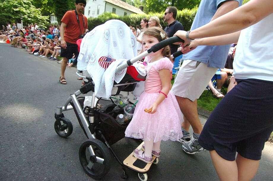 Hour Photo/ Alex von Kleydorff. Dressed for the parade, 2yr old Samantha Gannon gets a push from her parents.