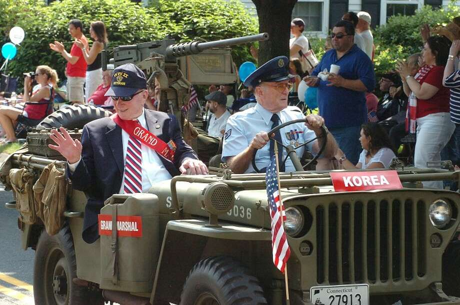 Hour Photo/ Alex von Kleydorff. Grand Marshal Robert Burns waves while driven by Bing Ventres in the Memorial Day Parade.