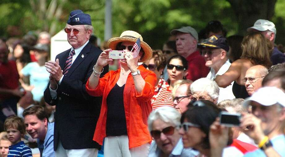 Hour Photo/ Alex von Kleydorff. First Selectman Bill Brennan applauds as wife Kathleeen takes a photo as the parade passes by