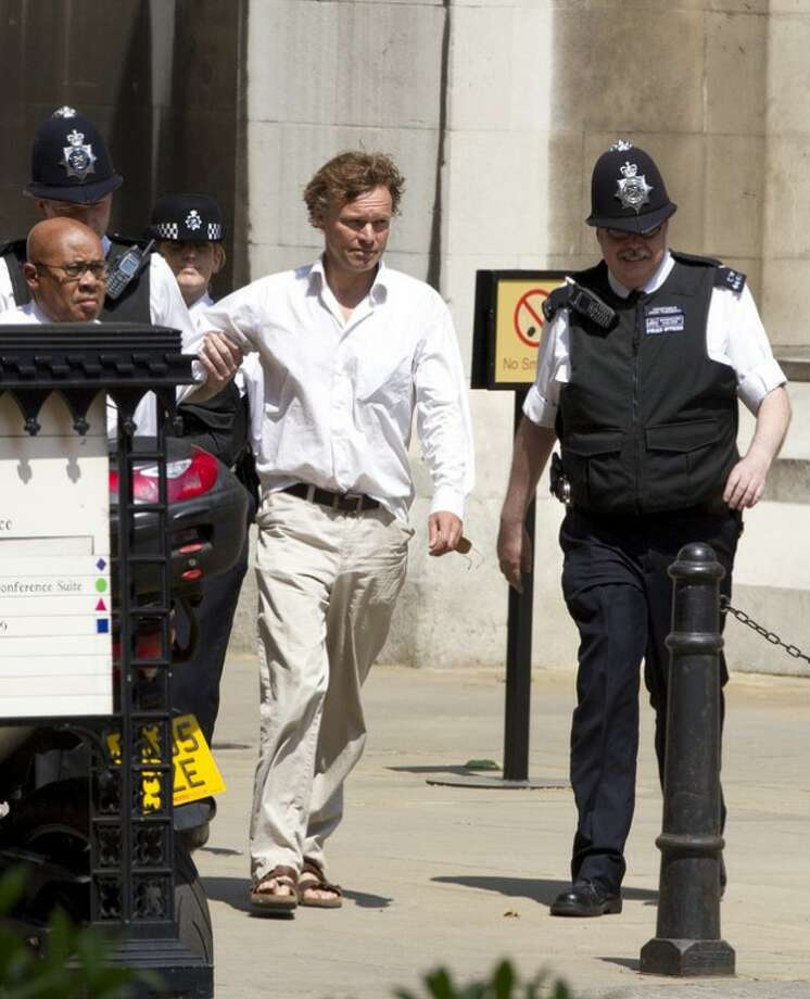 British police officers escort a man to a waiting police van after he heckled former British Prime Minister Tony Blair as he was giving evidence at the Leveson media inquiry at the Royal Courts of Justice in central London, Monday, May 28, 2012. The Leveson inquiry is Britain's media ethics probe that was set up in the wake of the scandal over phone hacking at Rupert Murdoch's News of the World, which was shut in July 2011 after it became clear that the tabloid had systematically broken the law. (AP Photo/Alastair Grant)