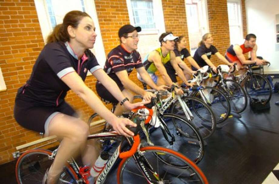 Photo/Alex von Kleydorff. Owner Julie Gabay takes part in a Computrainer class on bikes at Pacific Swim Bike Run in Stamford.