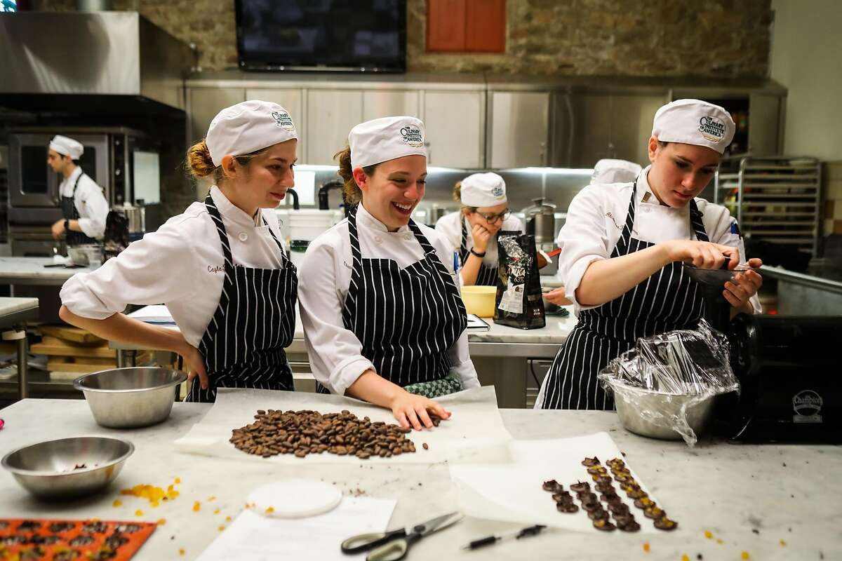 Students Cayla Taylor, Claudia LiCausi and Alex Marrano (left to right) winnow cacao beans the Culinary Institute of America in St. Helena.