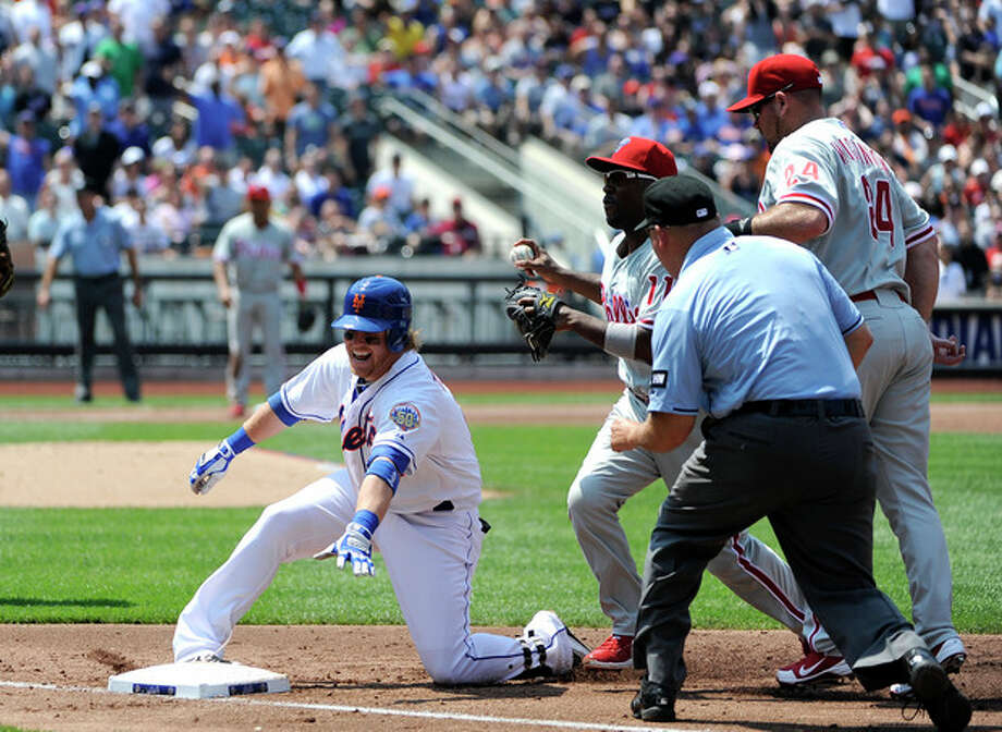 New York Mets' Justin Turner is picked off at first base by Philadelphia Phillies shortstop Jimmy Rollins as first baseman Ty Wigginton (24) watches at right in the third inning of a baseball game on Monday, May 28, 2012, at Citi Field in New York. Turner was injured on the play and taken out of the game. (AP Photo/Kathy Kmonicek) / FR170189 AP