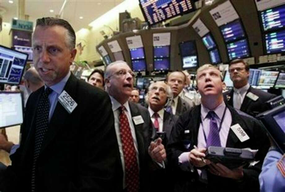 Specialist Donald Himpele Jr., left, directs trading in shares of Bank of America on the floor of the New York Stock Exchange Thursday, Aug. 25, 2011. (AP Photo/Richard Drew) / AP