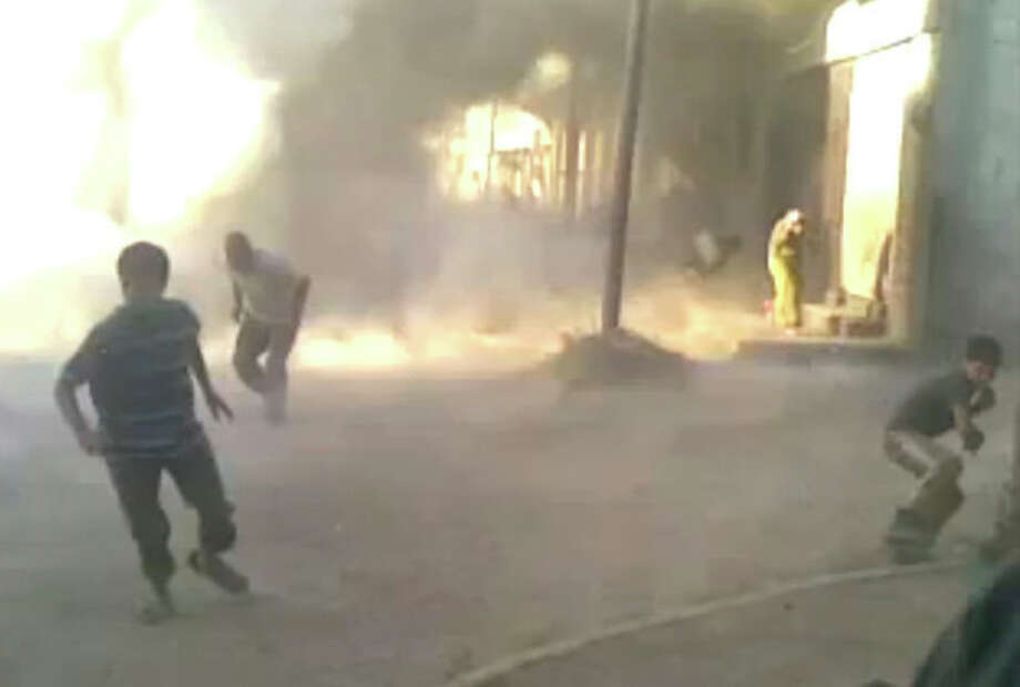 This frame grab made from an amateur video provided by Syrian activists on Monday, May 28, 2012, purports to show the massacre in Houla on May 25 that killed more than 100 people, many of them children. The amateur footage shows people running along a street, purportedly just after the attack on Houla started. (AP Photo/Amateur Video via AP video) THE ASSOCIATED PRESS IS UNABLE TO INDEPENDENTLY VERIFY THE AUTHENTICITY, CONTENT, LOCATION OR DATE OF THIS CITIZEN JOURNALISM IMAGE / Copyright 2012 The Associated Press. All rights reserved. This material may not be published, broadcast, rewritten or redistributed.