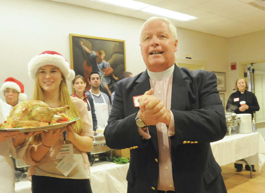Emma Mikesh holds the Christmas turkey as John Branson, rector of the Christ & Holy Trinity Church in Westport does the blessing before the feast which was open to the public. hour photo/Matthew Vinci / (C)2011, The Hour Newspapers, all rights reserved