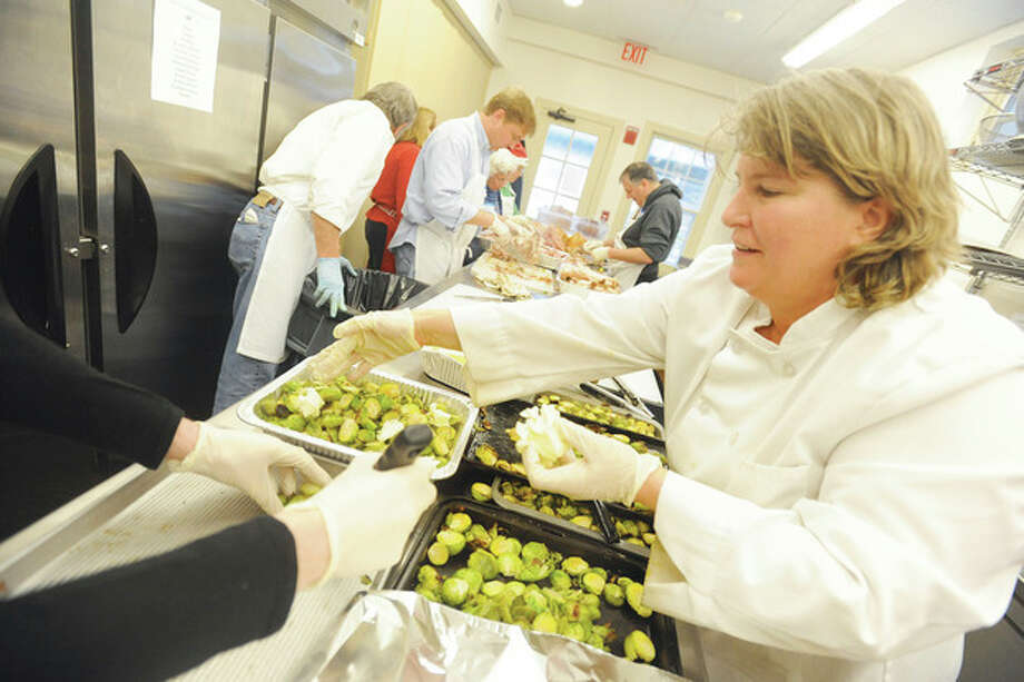 Head chef Paula Mikesh prepares the Christmas feast at Christ & Trinity Episcopal Church in Westport. The feast was open to the public in the name of the Saugatuck Congregational Church that was ravaged by fire . hour photo/Matthew Vinci / (C)2011, The Hour Newspapers, all rights reserved