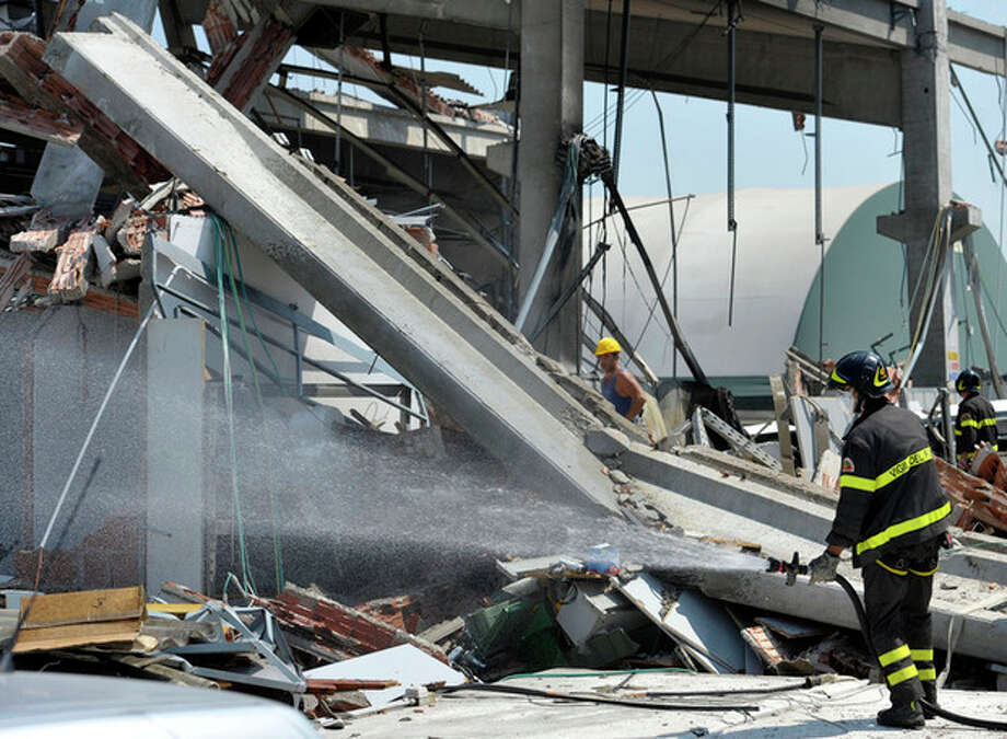 Italian firefighter sprays water on debris of a collapsed factory in Mirandola, northern Italy, Tuesday, May 29, 2012. A magnitude 5.8 earthquake struck the same area of northern Italy stricken by another fatal tremor on May 20. (AP Photo/Marco Vasini) / AP