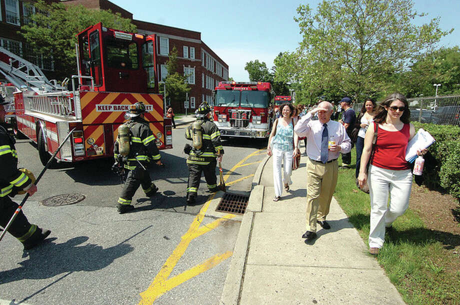 Hour photo / Alex von KleydorffNorwalk City Hall workers head back inside after being evacuated because of a fire alarm Tuesday afternoon. / 2012 The Hour Newspapers