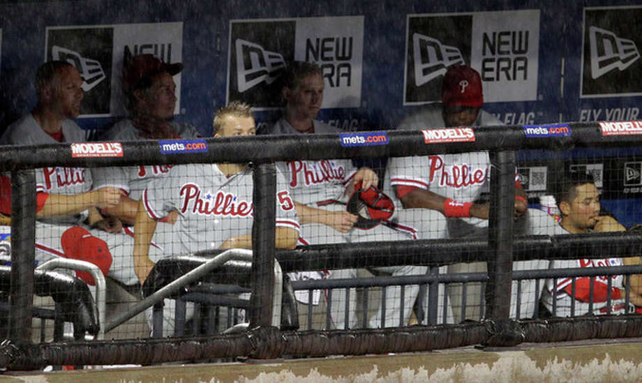 Philadelphia Phillies players wait out an eighth-inning rain delay during their baseball game against the New York Mets at Citi Field in New York, Tuesday, May 29, 2012. (AP Photo/Kathy Willens) / AP
