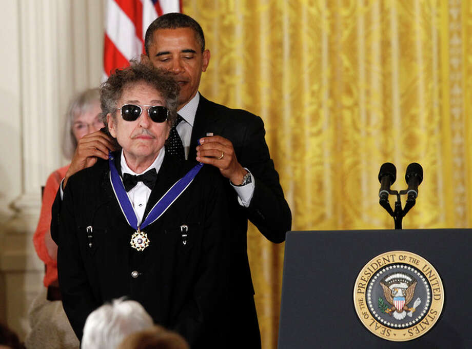 President Barack Obama presents rock legend Bob Dylan with a Medal of Freedom, Tuesday, May 29, 2012, during a ceremony at the White House in Washington. (AP Photo/Charles Dharapak) / AP