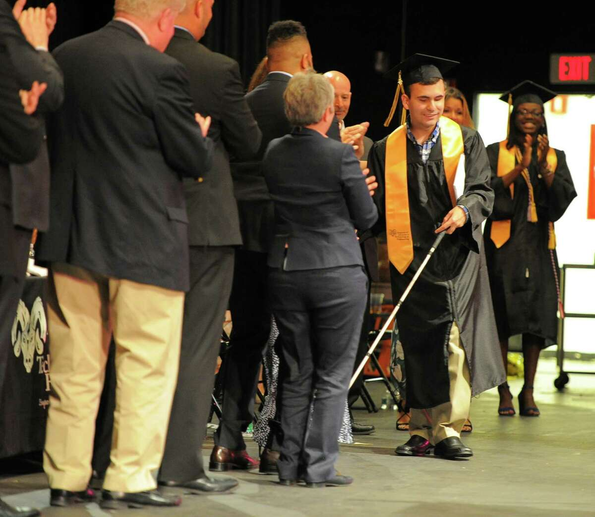 Brian Martin makes his way across stage as he is recognized with a standing ovation by his peers and audience during the Academy of Information Technology and Engineering Class of 2016 commencement at the school in Stamford, Conn., on Tuesday, June 14, 2016. Martin express it was his goal to navigate the stage unassisted when it came time to receiving his diploma.