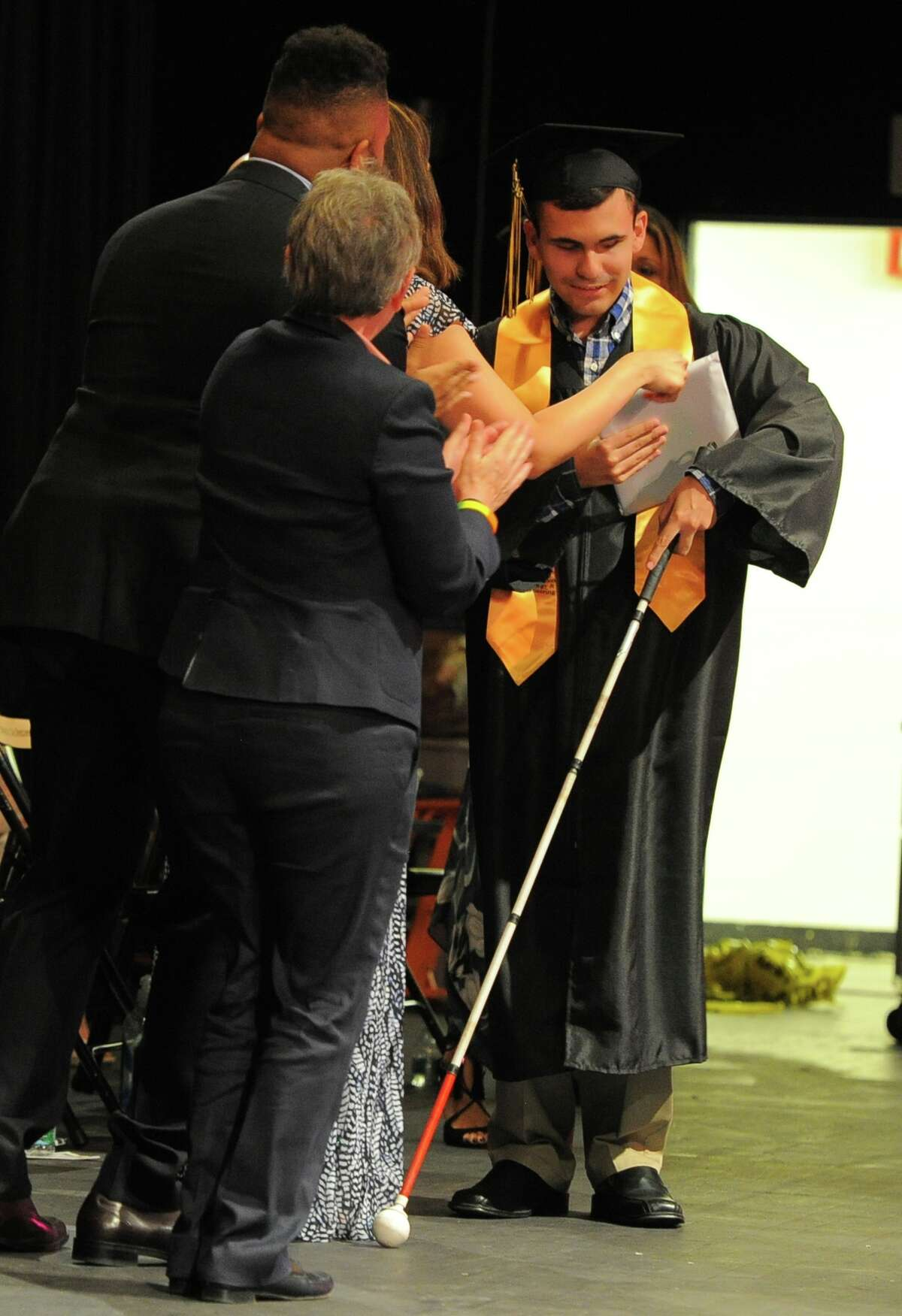Brian Martin his handed his diploma as he makes his way across stage to the cheers and sounds of a standing ovation by his peers and audience during the Academy of Information Technology and Engineering Class of 2016 commencement at the school in Stamford, Conn., on Tuesday, June 14, 2016. Martin express it was his goal to navigate the stage unassisted when it came time to receiving his diploma.