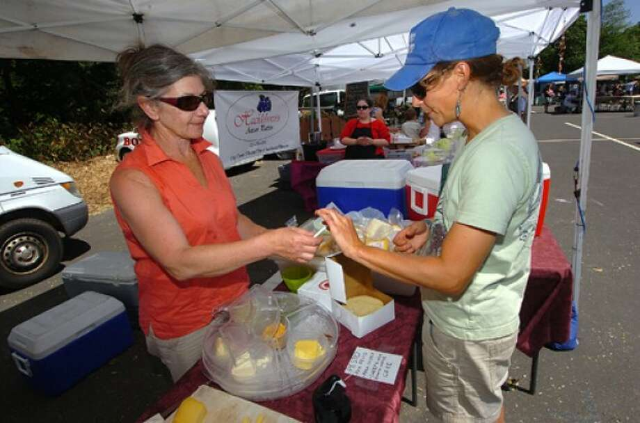 Photo by Alex von Kleydorff. Jeannette Pringle passes samples of their artisan Sheeps milk riccotta chese fresh from Sankows Beaver Brook Farm in Lyme Ct. at the Werstport Farmers Market