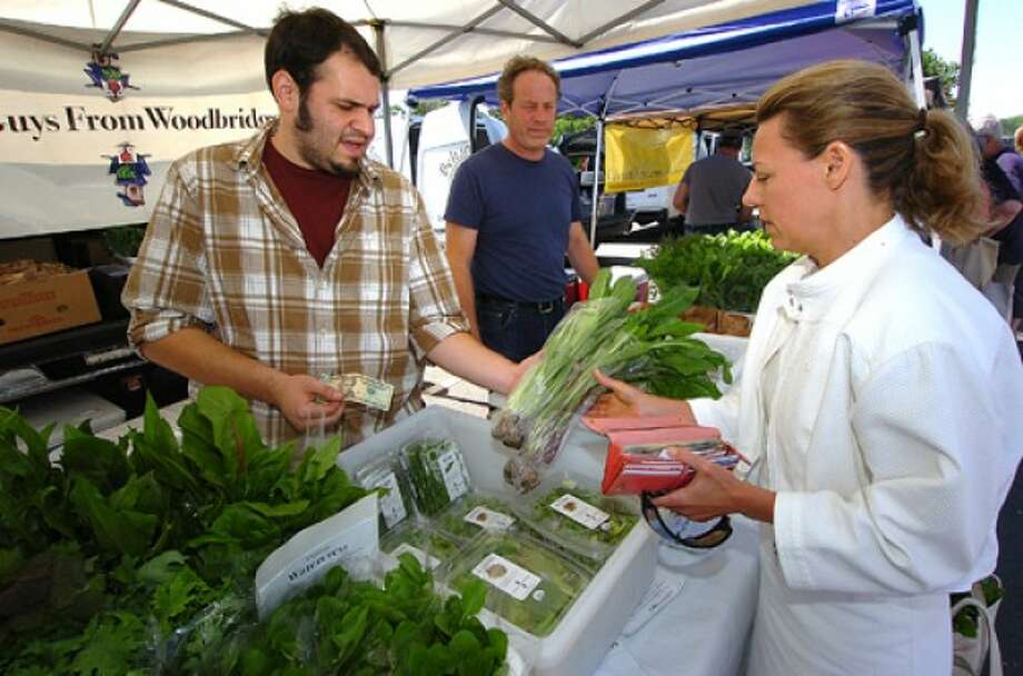 Photo by Alex von Kleydorff. Courtnay Arpano from Greenwich buys bunches of Organic Italian Dandelion Greens for a Tabouli dish from the Two guys from Woodbridge booth.
