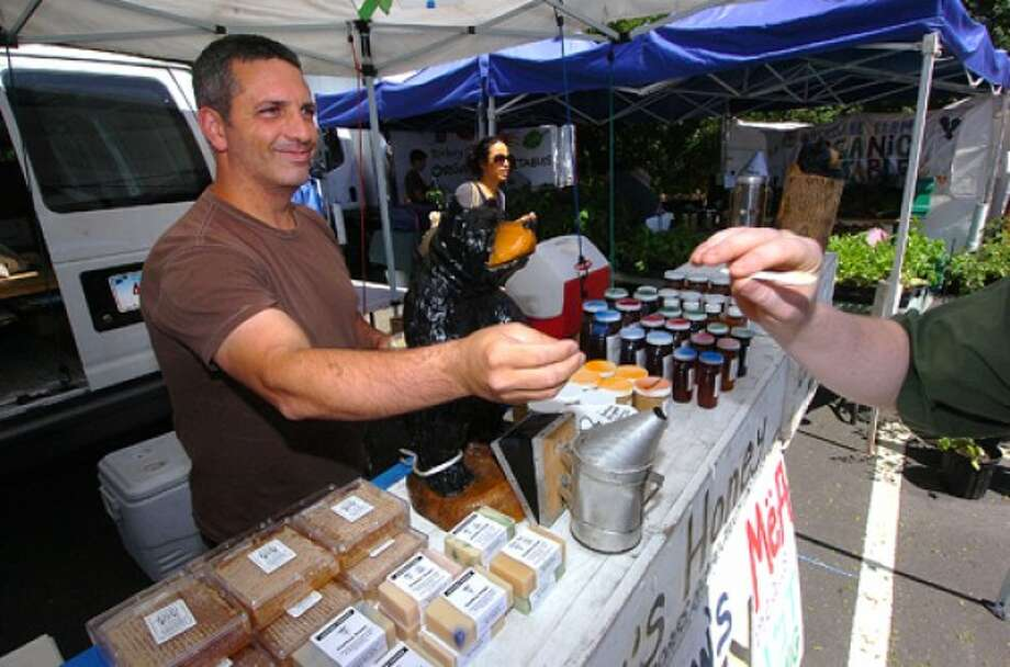 Photo by Alex von Kleydorff. Andrew Cote passes out spoonfulls of his whipped honey from his Andrews Local Honey stand at The Westport farmers market
