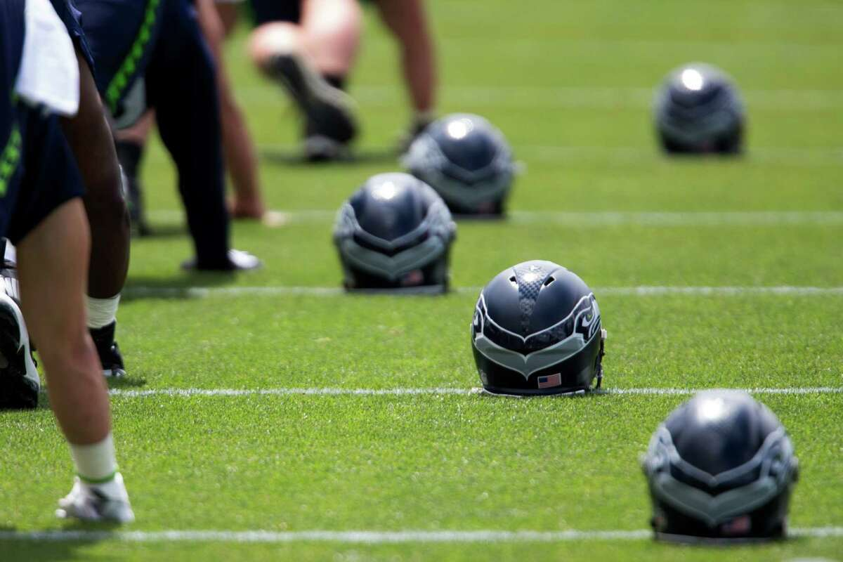 Seahawks helmets wait next to their corresponding player as they stretch before minicamp at Virginia Mason Athletic Center in Renton, Wa., Tuesday, June 14, 2016.