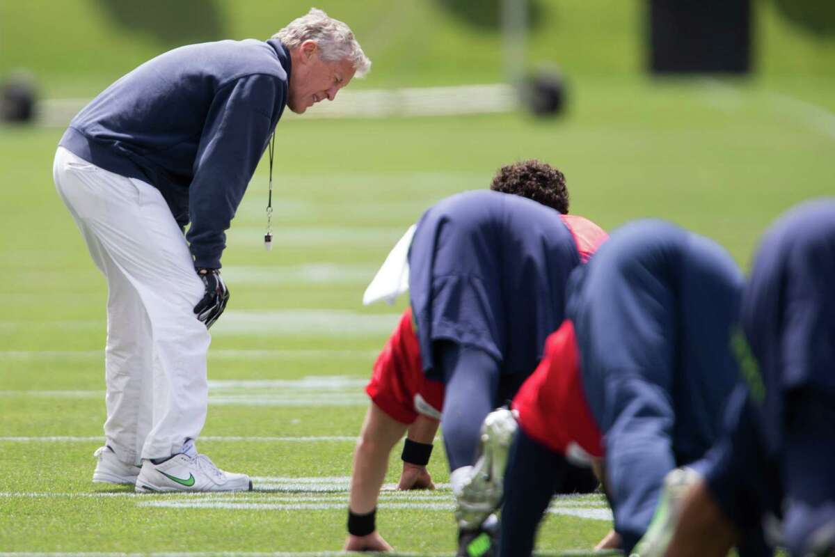 Seahawks head coach Pete Carroll talks with quarterback Russell Wilson during minicamp at Virginia Mason Athletic Center in Renton, Wa., Tuesday, June 14, 2016.