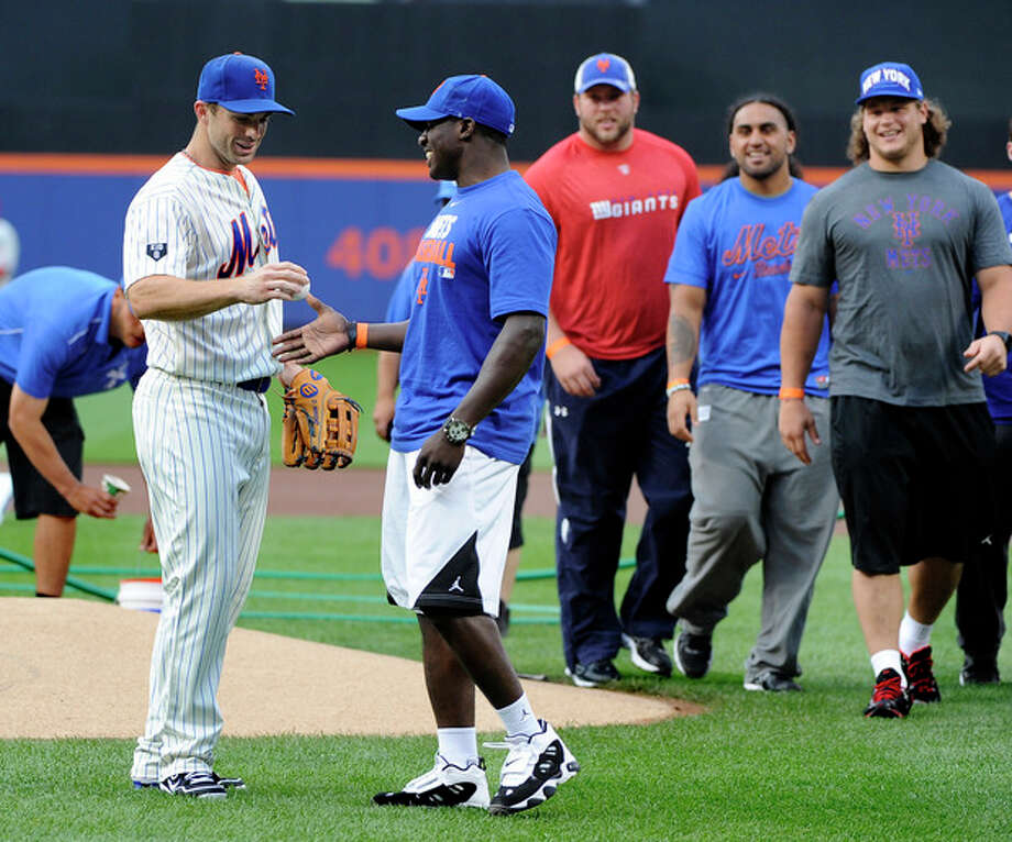 New York Giants rookies watch New York Mets third baseman David Wright present first round draft pick David Wilson with a baseball after Wilson threw out the first ceremonial pitch before the baseball game between the Philadelphia Phillies and New York Mets on Wednesday, May 30, 2012, at Citi Field in New York. (AP Photo/Kathy Kmonicek) / FR170189 AP