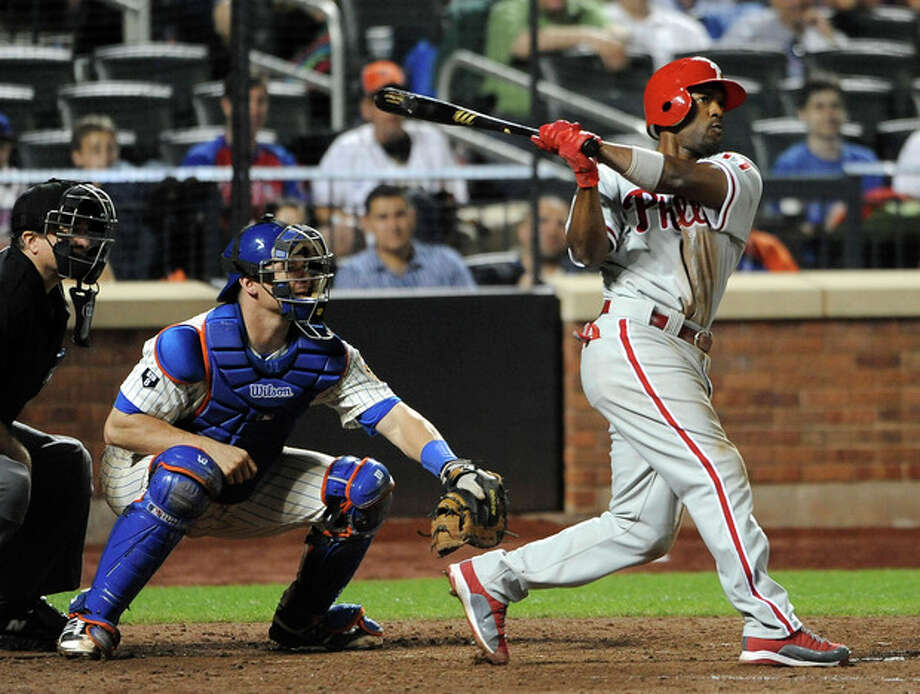 Philadelphia Phillies' Jimmy Rollins hits a three-run home run off of New York Mets relief pitcher Ramon Ramirez as Mets' Rob Johnson catches in the ninth inning of a baseball game on Wednesday, May 30, 2012, at Citi Field in New York. (AP Photo/Kathy Kmonicek) / FR170189 AP