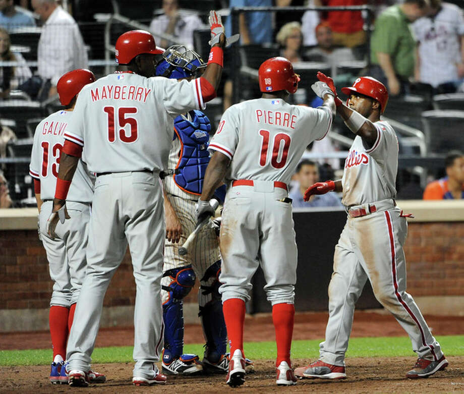 Philadelphia Phillies' Jimmy Rollins is greeted at home plate by Freddy Galvis (13), John Mayberry Jr. (15) and Juan Pierre (10) after hitting a three-run home run off of New York Mets relief pitcher Ramon Ramirez that score Galvis and Mayberry in the ninth inning of a baseball game on Wednesday, May 30, 2012, at Citi Field in New York. (AP Photo/Kathy Kmonicek) / FR170189 AP