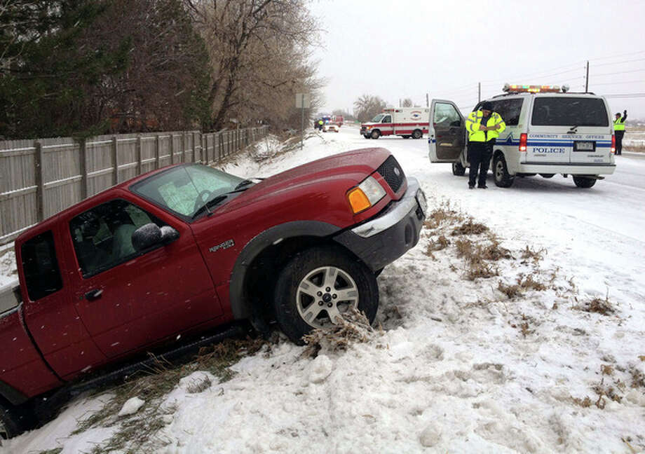 Longmont police respond to three separate weather-related accidents as snow falls on Colo. Hwy. 66 at Francis Street in Longmont, Colo., on Monday, Dec. 19, 2001. A major storm is bringing blizzard conditions to Colorado's southeastern corner, where ranches and farms have been hit hard by drought. (AP Photo/Longmont Times-Call, Richard M. Hackett) BOULDER DAILY CAMERA OUT; COLORADO DAILY OUT / The Daily Times Call