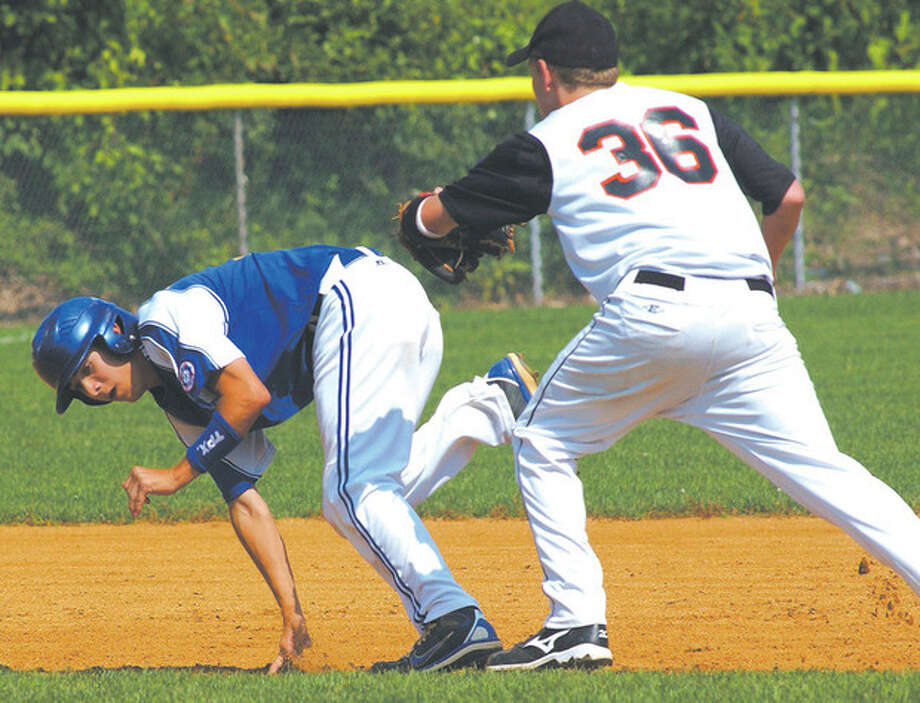 norwalkbr2.jpg - john nash photo - Norwalk's Bryan Daniello, left, tries to keep his balance as he is tagged out by Ridgefield's Danny Lake on Saturday.