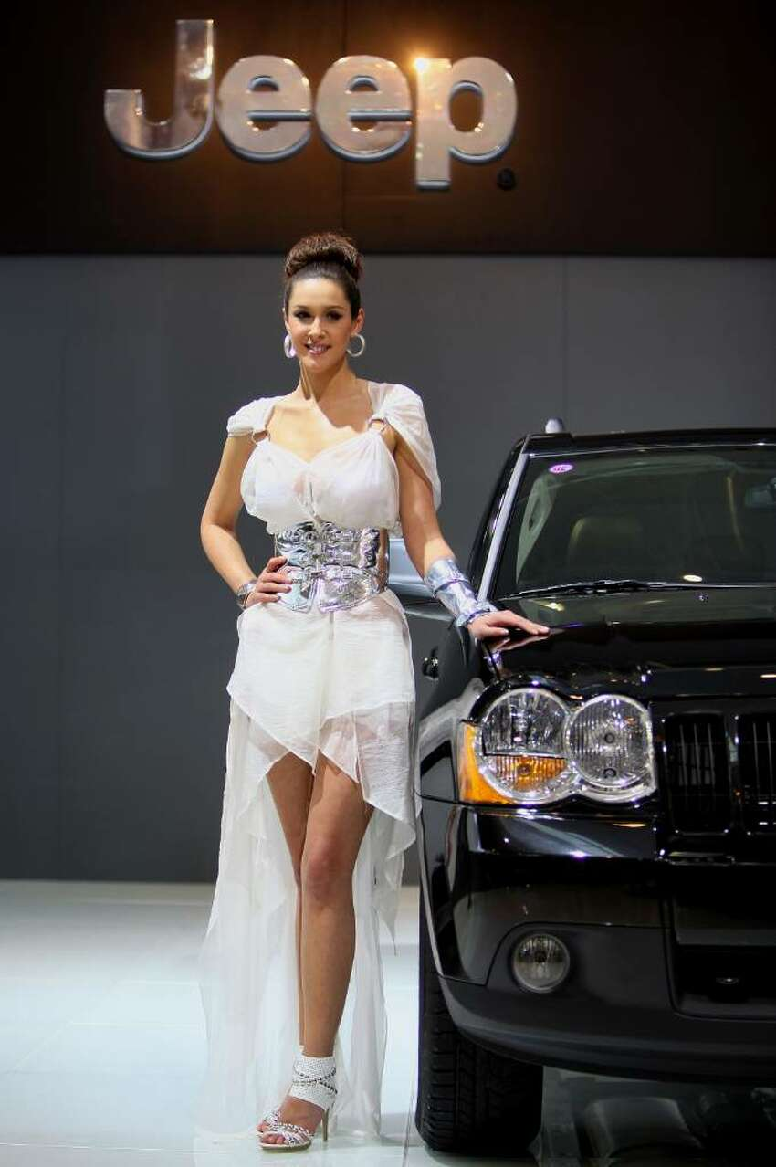 BEIJING - APRIL 23: A model stands beside Jeep Grand Cherokee during a special media opening of the Beijing Auto Show on April 23, 2010 in Beijing of China. Major global automakers plan to unveil dozens of new models at the Beijing auto show, which has quickly become one of the biggest and most important auto shows in the world and raises its curtains on Friday and will last till May 2, during which 990 models - with 89 making their global debut - will be displayed in a 200,000-sq-m area. (Photo by Feng Li/Getty Images)