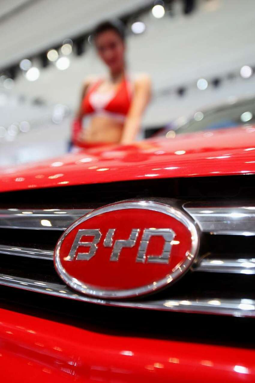 BEIJING - APRIL 23: A model stands beside China's BYD car during a special media opening of the Beijing Auto Show on April 23, 2010 in Beijing of China. Major global automakers plan to unveil dozens of new models at the Beijing auto show, which has quickly become one of the biggest and most important auto shows in the world and raises its curtains on Friday and will last till May 2, during which 990 models - with 89 making their global debut - will be displayed in a 200,000-sq-m area. (Photo by Feng Li/Getty Images)