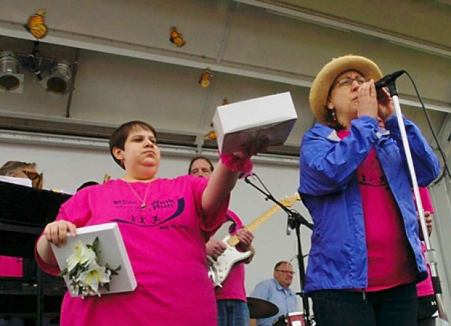 Cancer survivor Ivannia Mena lets the ceremonial butterflies loose while Norwalk Hospital adjunct chaplain Lynn Krager addresses the crowd at the Whittingham Cancer Center''s annual 3K walk and 5K run at Norwalk''s Calf Pasture Beach Saturday. Hour photo / Erik Trautmann
