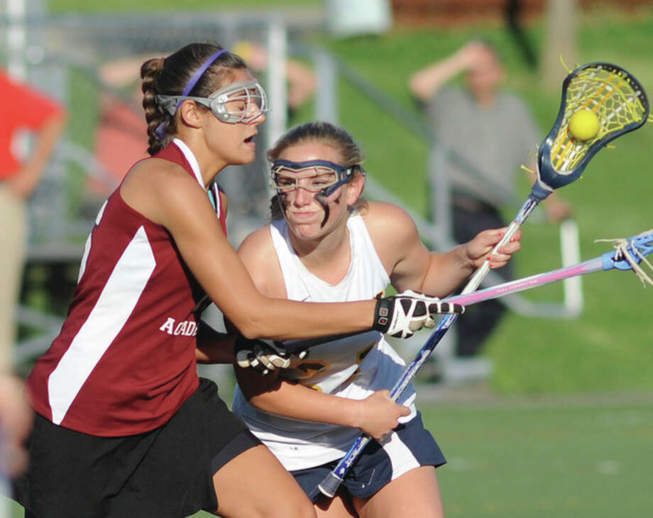 Hour photo/John NashWeston's Catie Ledwick, right, protects the ball against the defense of Sacred Heart Academy's Alex Ryan during Thursday's CIAC Class S girls lacrosse playoff game in Weston.