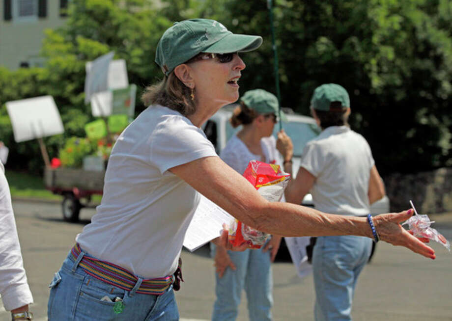 Margaret Killip tosses candy to the crowd as she marches for the Rowayton Gardeners Club during Rowayton's annual Memorial Day Parade Sunday morning.Hour Photo / Danielle Robinson