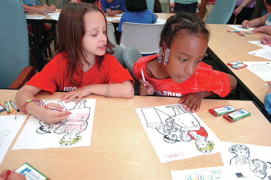 Hour Photo/ Alex von Kleydorff. Wolfpit School second graders Demetra Christa and Eyja Bledsoe color some hospital images during their Read-A-Thon visit / 2012 The Hour Newspapers
