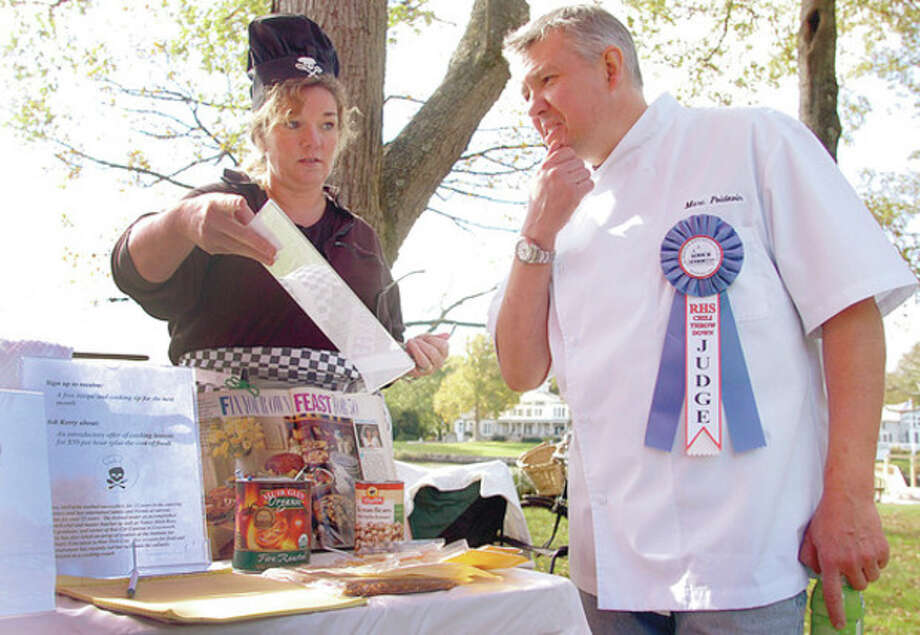 Above left, Kerry McFarlin gets judged by Marc Poidevin of Rowayton Market at the Chili Throwdown. Above right, David McCart serves up chili. / (C)2011, The Hour Newspapers, all rights reserved