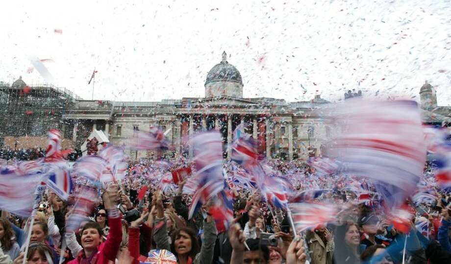 Royal fans wave flags in Trafalgar Square as they watch the wedding of Britain''s Prince William and Kate Middleton,in Trafalgar Square in London on Friday, April 29, 2011. (AP Photo/Simon Dawson)