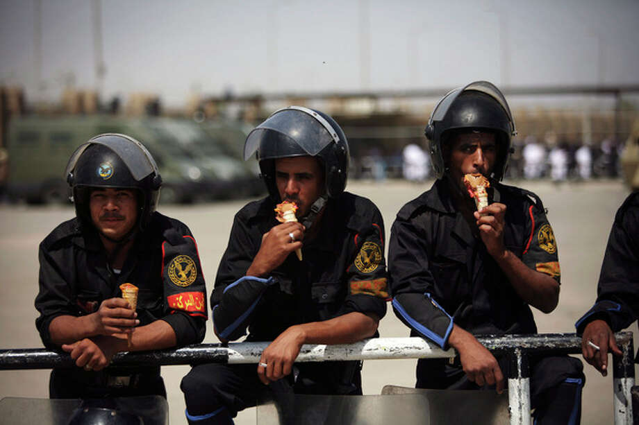 Egyptian riot police eat ice cream while securing the courthouse where ex-President Hosni Mubarak received a verdict in his trial for charges related to the death of protesters in Cairo, Egypt, Saturday, May 2, 2012. Egypt's ex-President Hosni Mubarak was sentenced to life in prison Saturday for his role in the killing of protesters during last year's revolution that forced him from power, a verdict that caps a stunning fall from grace for a man who ruled the country as his personal fiefdom for nearly three decades. (AP Photo/Manu Brabo) / AP