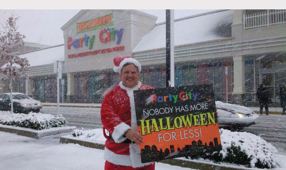 "Party City won't let the snow ice Halloween this year. Vice President of Marketing Bill Furtkevic dons a Santa Suit to wish revelers a ""Merry Halloween."" With more than 700 stores open until midnight tonight, late Sunday and on Halloween, there is still time to stock up on costumes and party supplies before the big day. Go to PartyCity.com for coupons and deals. (PRNewsFoto/Party City) / PARTY CITY"