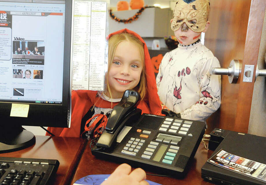 Hour photos /Matthew Vinci Maddie O'Neill, 5, and her brother Luke, 8, of Wilton, trick or treat at Charkit Chemical corporation in Norwalk Monday. The company set up stations in the office for kids in towns where Halloween was postponed. / (C)2011, The Hour Newspapers, all rights reserved