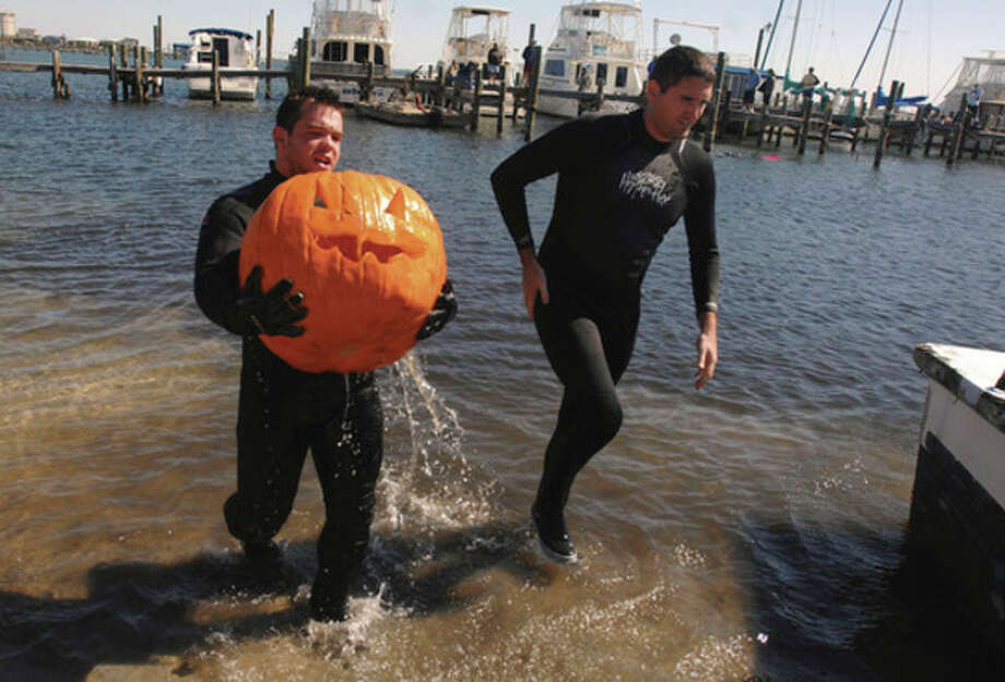 In this Saturday, Oct. 29, 2011 photo, Chris Hicks carries a carved pumpkin from the water with his partner Clint Murphy during the underwater pumpkin carving contest at Grand Lagoon Yacht Club in Pensacola, Fla. (AP Photo/The Pensacola News Journal, John Blackie) NO SALES / The Pensacola News Journal