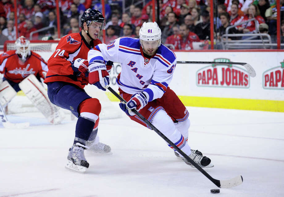 New York Rangers left wing Rick Nash (61) works the puck against Washington Capitals defenseman John Carlson (74) during the second period of an NHL hockey game, Sunday, March 10, 2013, in Washington. (AP Photo/Nick Wass) / FR67404 AP