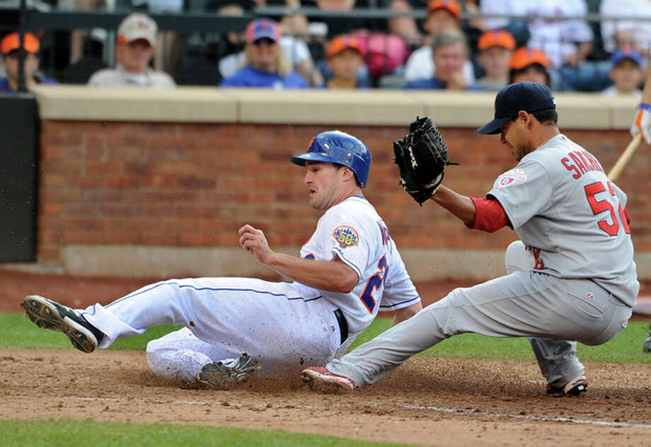 New York Mets' Daniel Murphy,left, scores at home plate past St. Louis Cardinals relief pitcher Eduardo Sanchez (52) on a wild pitch in the seventh inning of a baseball game on Saturday, June 2, 2012, at Citi Field in New York. (AP Photo/Kathy Kmonicek) / FR170189 AP