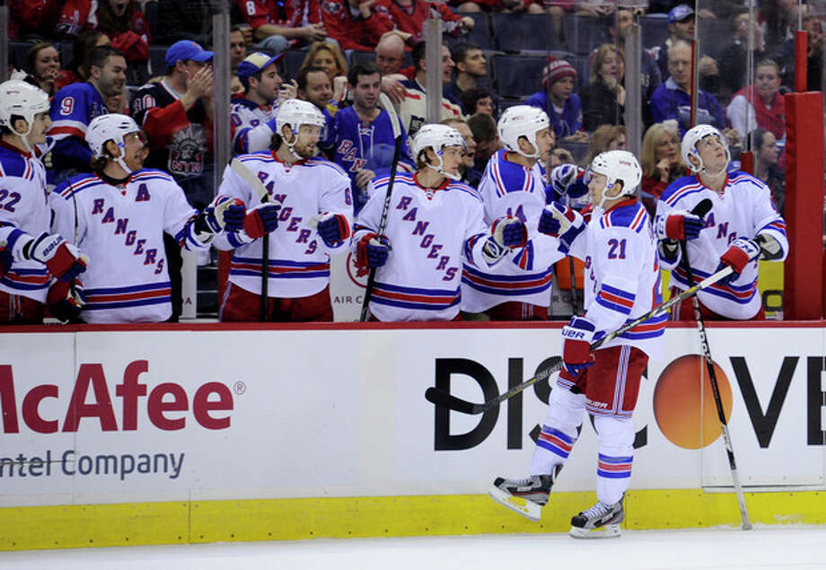 New York Rangers center Derek Stepan (21) celebrates his goal with the bench against the Washington Capitals during the first period of an NHL hockey game, Sunday, March 10, 2013, in Washington. (AP Photo/Nick Wass) / FR67404 AP