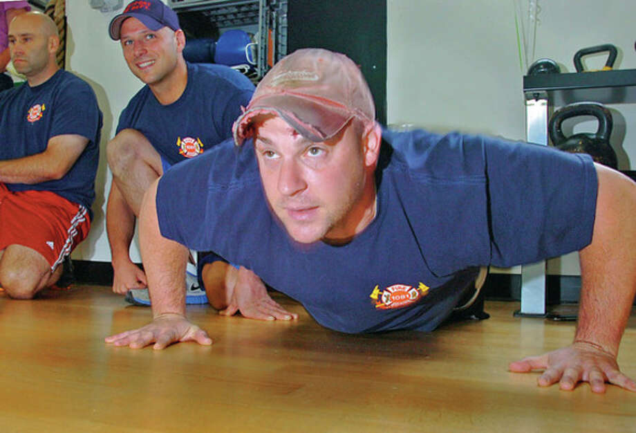 Westport Police compete against firefighters including Joe Micaliezzi, Ted Crawford and Jay Kronenberger in a push-up contest to benefit the Hole in the Wall Gang at the Fitness Factory of Westport Saturday.Hour photo / Erik Trautmann / (C)2012, The Hour Newspapers, all rights reserved