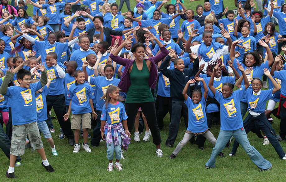 First lady Michelle Obama hosts local children on the South Lawn of the White House in Washington, Tuesday, Oct. 11, 2011, as they attempt to break the Guinness World Records title for the most people doing jumping jacks in a 24-hour period. (AP Photo/Pablo Martinez Monsivais) / AP