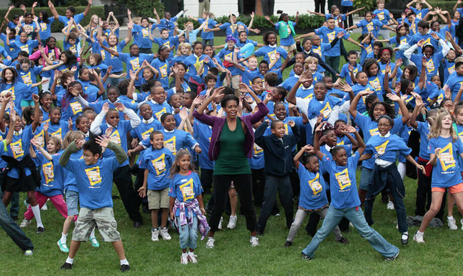 First lady Michelle Obama hosts local children on the South Lawn of the White House in Washington, Tuesday,Oct. 11, 2011, as they attempt to break the Guinness World Records title for the most people doing jumping jacks in a 24-hour period. (AP Photo/Pablo Martinez Monsivais) / AP