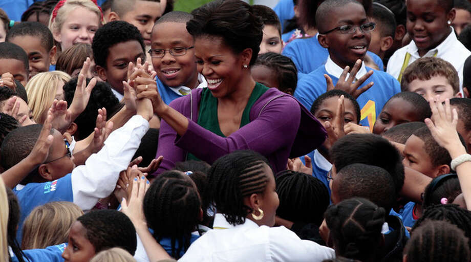 First lady Michelle Obama hosts local children on the South Lawn of the White House in Washington as they attempt to break the Guinness World Records title for the most people doing jumping jacks in a 24-hour period, Tuesday, Oct., 11, 2011. (AP Photo/Pablo Martinez Monsivais) / AP